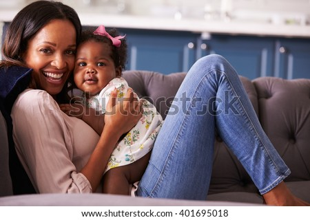 Portrait of woman relaxing at home with her toddler daughter - stock photo