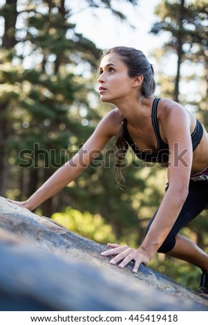 Portrait of woman rock climbing on the wood