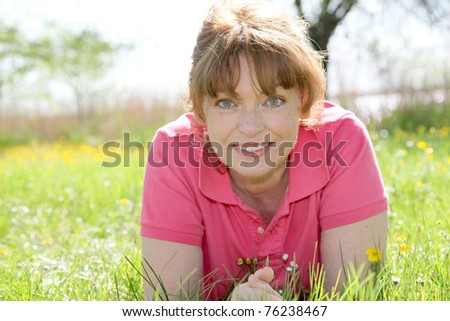 portrait of woman senior laying in grass - stock photo