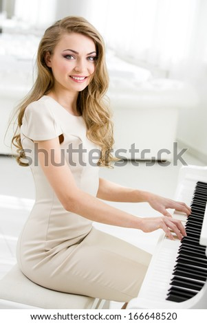Portrait of woman sitting and playing piano. Concept of music and art - stock photo