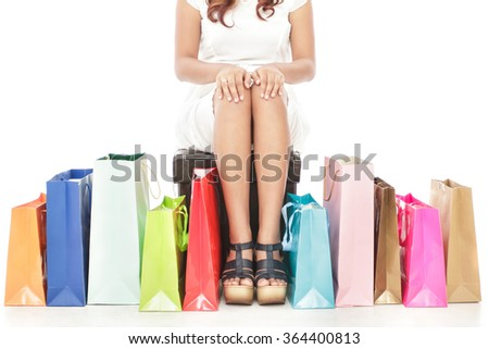 portrait of woman sitting between multicolor shopping bags isolated on white background