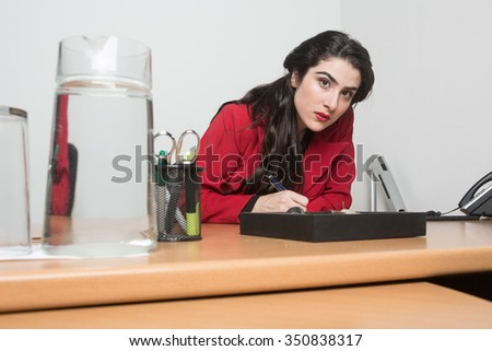 Portrait of woman sitting in the office writing looking at the camera serious.