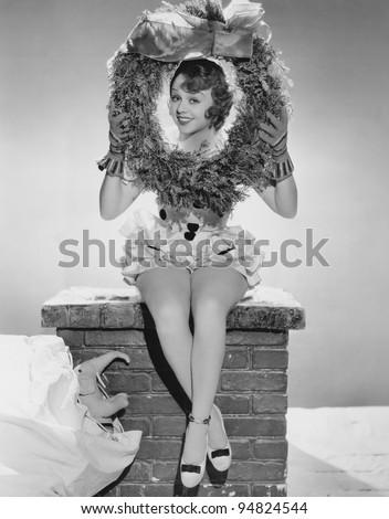 Portrait of woman sitting on chimney holding Christmas wreath - stock photo