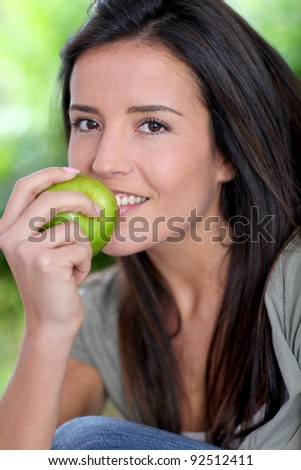 Portrait of woman sitting outside with apple
