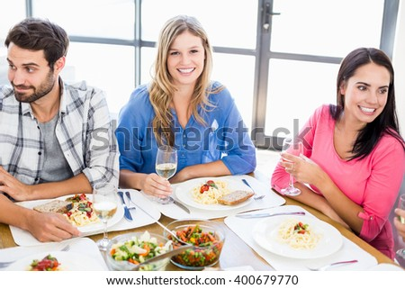 Portrait of woman sitting with friends at dinning table while having meal - stock photo