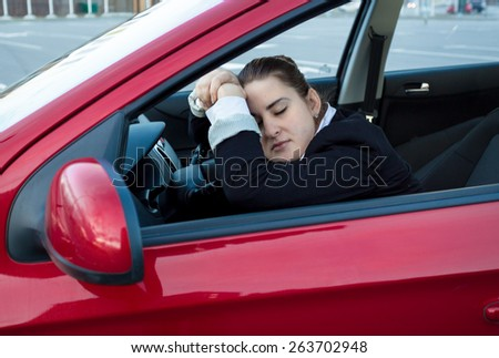 Portrait of woman sleeping in car on drivers seat - stock photo