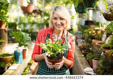 Portrait of woman smiling while holding potted plant at greenhouse