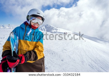 Portrait of woman snowboarder on background beautiful landscape of snowy high mountains of Caucasus at Krasnaya Polyana, standing with snowboard