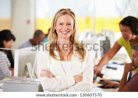 Portrait Of Woman Standing In Busy Creative Office - stock photo
