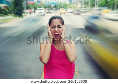 Portrait of woman standing still in the middle of a street with cars passing by fast, screaming stressed and frustrated  - stock photo