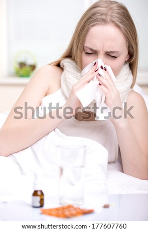 Portrait of woman suffering from cold in bed - stock photo