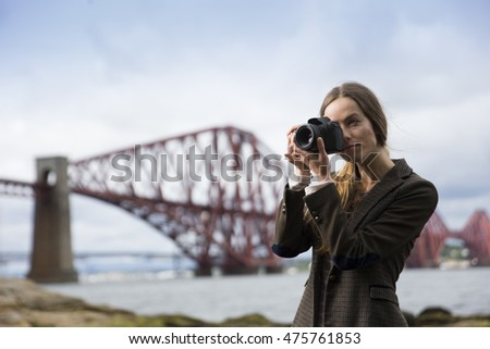 Portrait of woman taking landscape photos with a Camera of The Forth Bridge at Queensferry, Scotland.