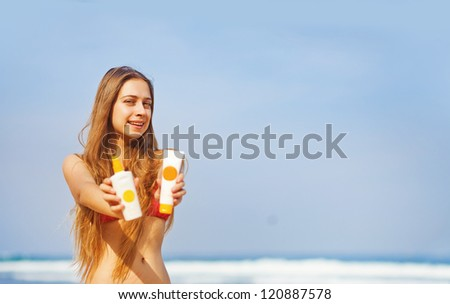 Portrait of woman taking skincare with sunscreen lotion at beach - stock photo