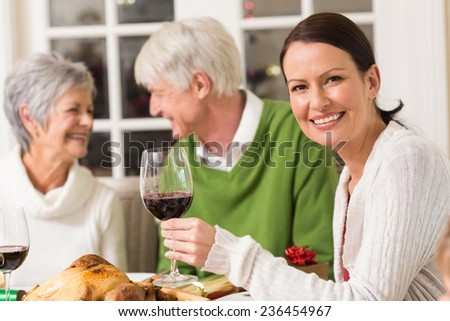 Portrait of woman toasting at camera during christmas dinner at home in the living room