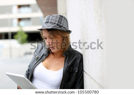 Portrait of woman using tablet in town