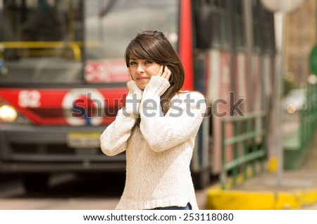 portrait of woman walking on the city street covering her ears concept of noise pollution - stock photo