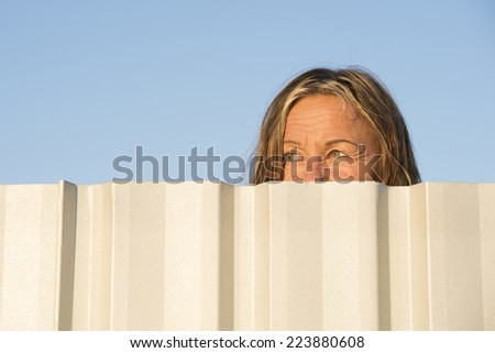 Portrait of woman watching, observing hiding behind neighbor metal fence outdoor, with blue sky as background and copy space - stock photo