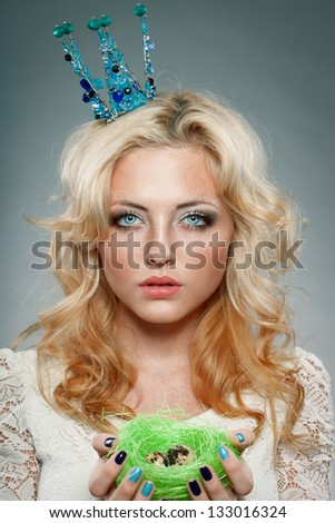 portrait of woman wearing  blue princess crown and holding nest with quail eggs - stock photo