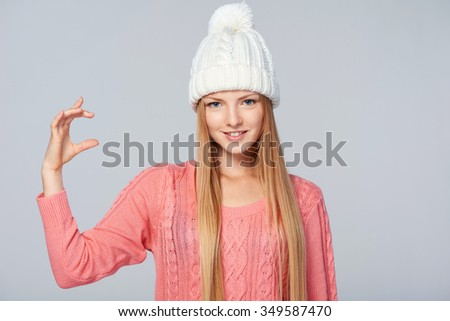 Portrait of woman wearing warm winter clothing holding imaginary product in her fingers, over gray background