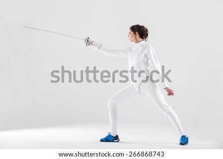 Portrait of woman wearing white fencing costume practicing with the sword