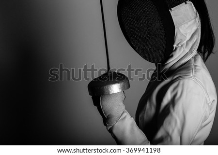 Portrait of woman wearing white fencing costume practicing with the sword. Black And white. - stock photo