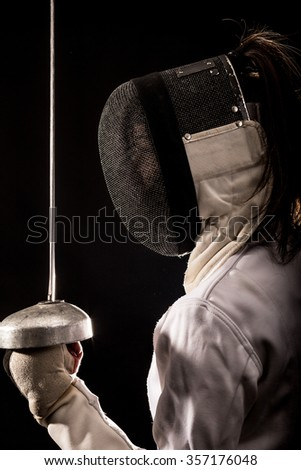 Portrait of woman wearing white fencing costume practicing with the sword. Isolated on black background. - stock photo