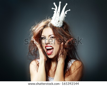 portrait of woman wearing white princess crown with funny and crazy expression on her face - stock photo