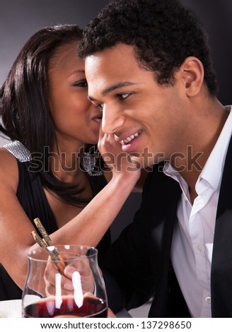 Portrait Of Woman Whispering To Boyfriend's Ear At Dinner
