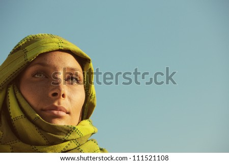 Portrait of woman with a green turban against blue sky, copy space - stock photo
