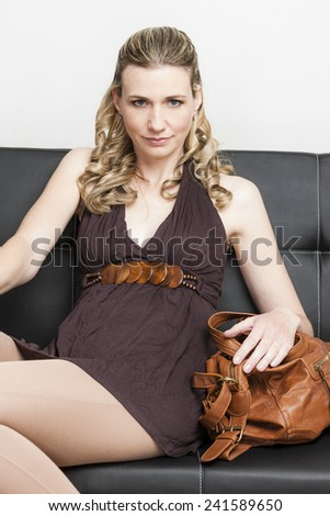 portrait of woman with a handbag sitting on sofa - stock photo