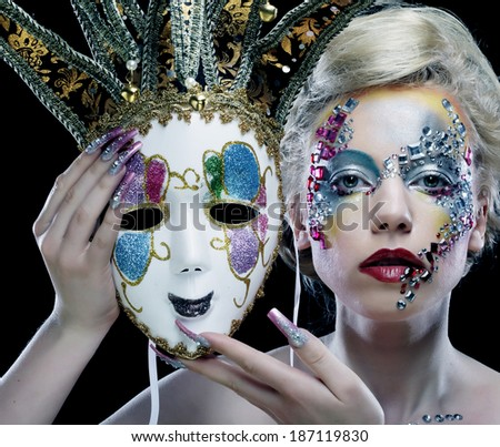 Portrait of woman with artistic make-up holding mask - stock photo