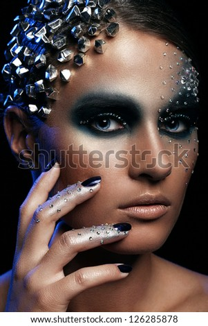 Portrait of woman with artistic make-up isolated over black background - stock photo