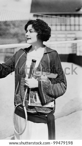 Portrait of woman with badminton racket and magazine - stock photo