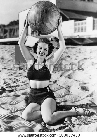 Portrait of woman with ball at beach - stock photo