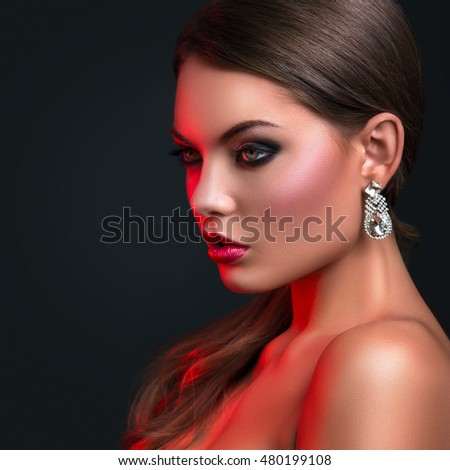 Portrait of woman with beautiful earrings in red light