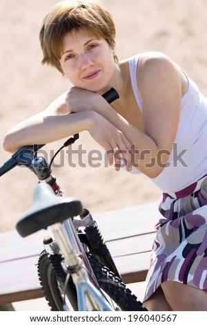 Portrait of woman with bicycle against sand beach