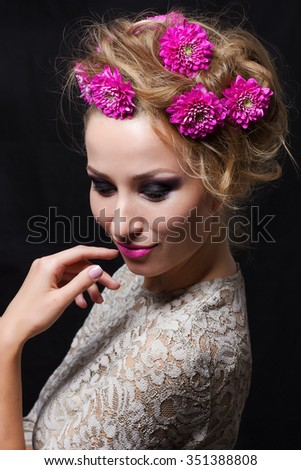Portrait of woman with chrysanthemums in blonde hair with close eyes