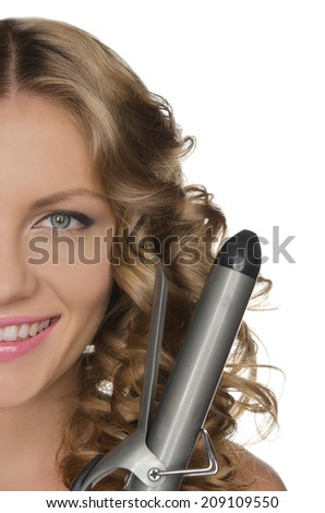 Portrait of woman with curly hair and tool for tightening hair - stock photo