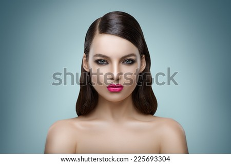 Portrait of woman with curly hair on blue background - stock photo