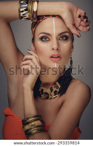 Portrait of woman with exotic make up. Bracelets on hands and orange leopard pattern on bandana. - stock photo