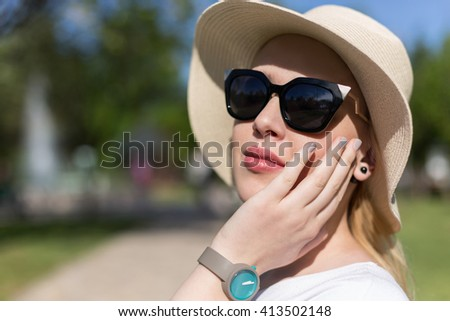 Portrait of woman with hat and sunglassess outside