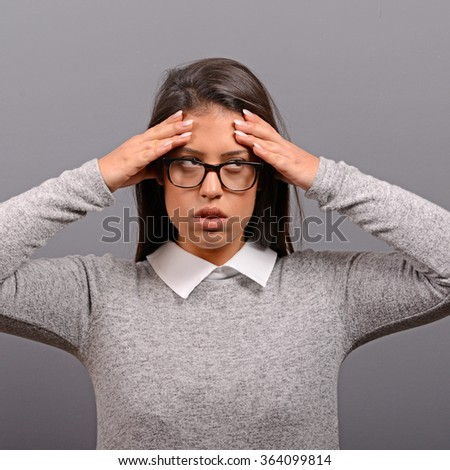 Portrait of woman with headache against gray background - stock photo