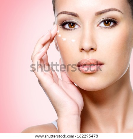 Portrait of woman with healthy face applying cosmetic cream under the eyes - stock photo