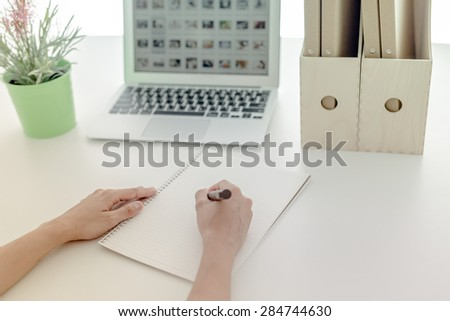 Portrait of woman with laptop writes on a document - stock photo
