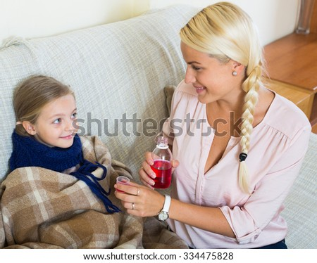 Portrait of woman with liquid medicine and child having influenza