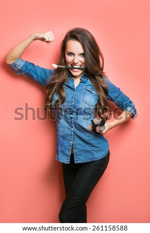 portrait of woman with makeup brush in a mouth. beauty and power concept - stock photo