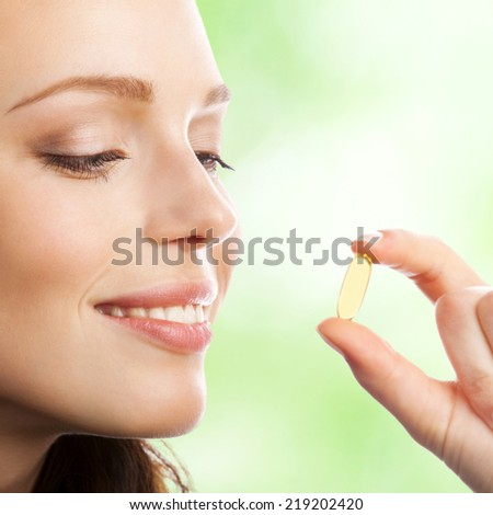 Portrait of woman with Omega 3 fish oil capsule, outdoor - stock photo