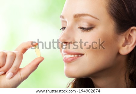 Portrait of woman with Omega 3 fish oil capsule, outdoors - stock photo