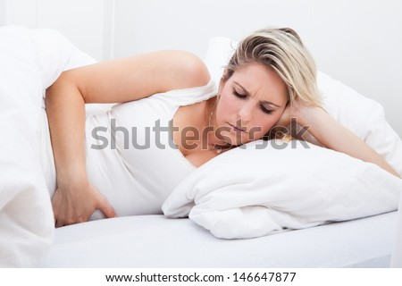 Portrait of woman with stomach ache lying on bed