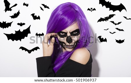 Portrait of woman with terrifying halloween makeup and purple wig over white background. Flying bats